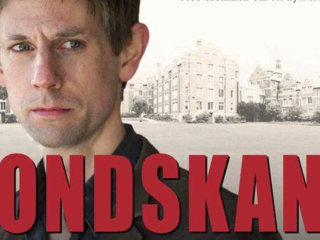 Banner med Ondskan i stora röda bokstäver, och en man ed bistert uttryck bakom.