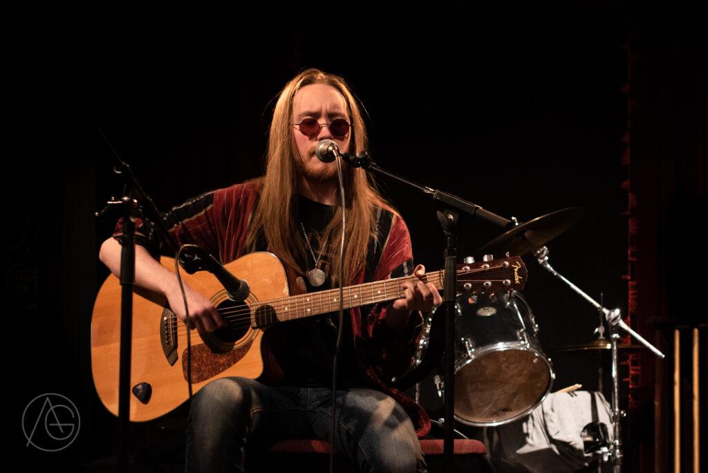 Man på scen som sjunger och spelar gitarr.